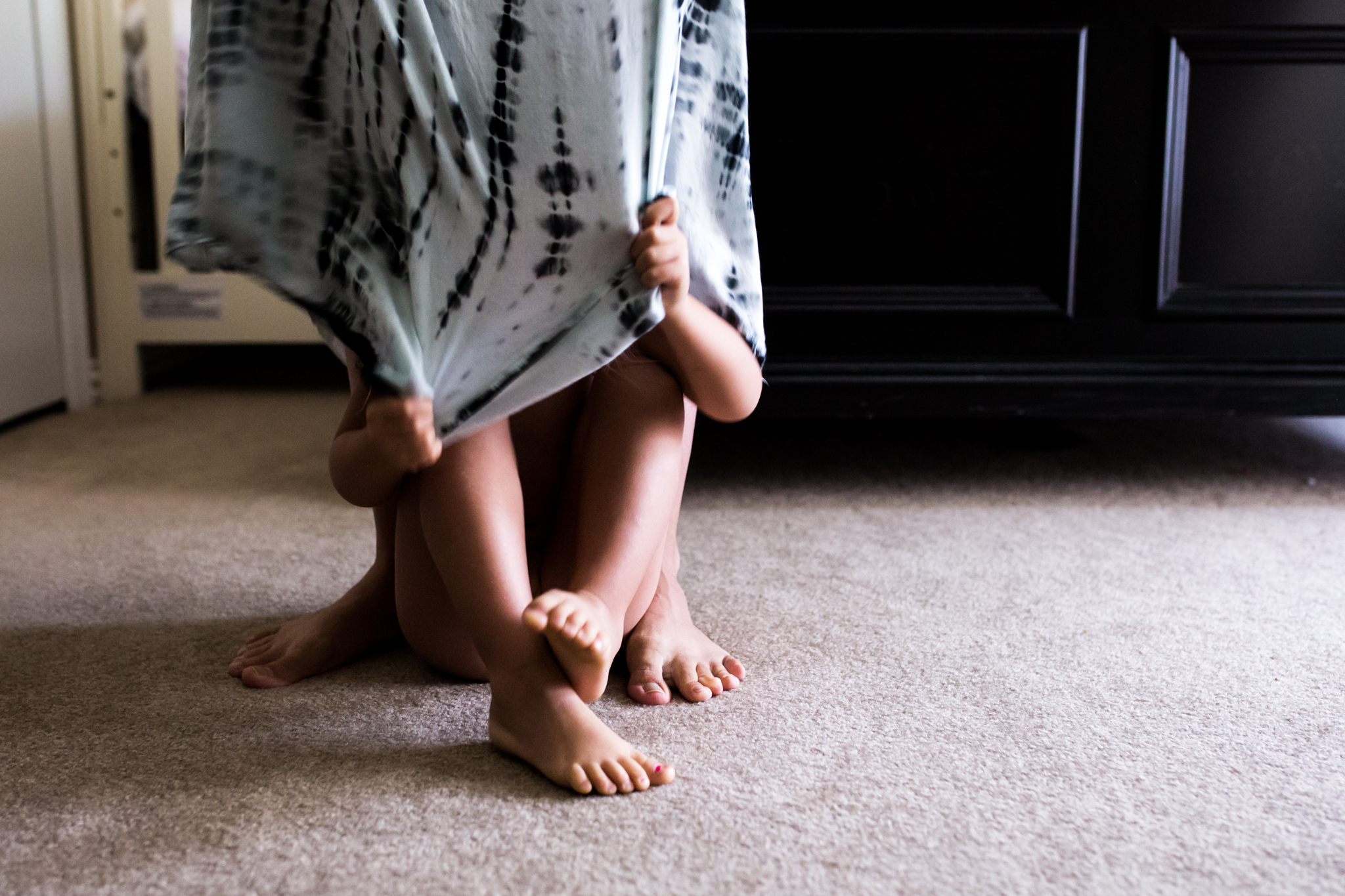 During a Day In The Life Session in Farmers Branch, Texas, Lawren Rose Photography takes a photograph of a little girl hiding under her mothers dress and playing around