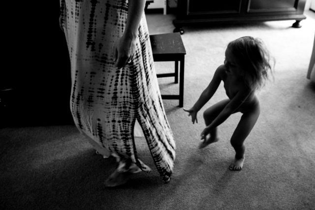 Lawren Rose Photography takes a photograph of a little girl running naked to get under her mothers dress during a Day In The Life session