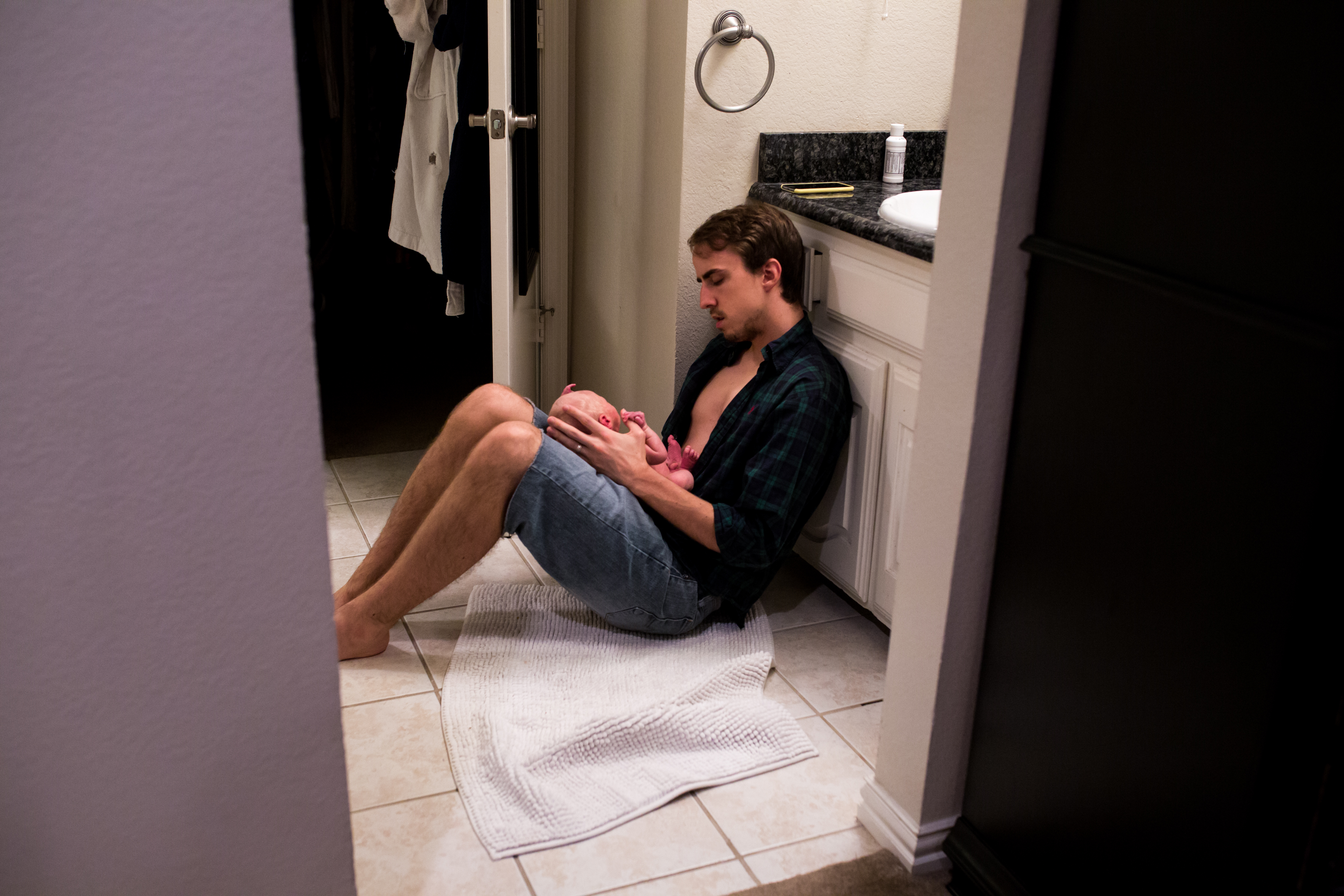 Lawren Rose Photography sneaks a sweet photograph of a dad sitting on the bathroom floor holding his newborn son on his knees as he admires his bundle of joy during a family photography session in farmers branch, texas