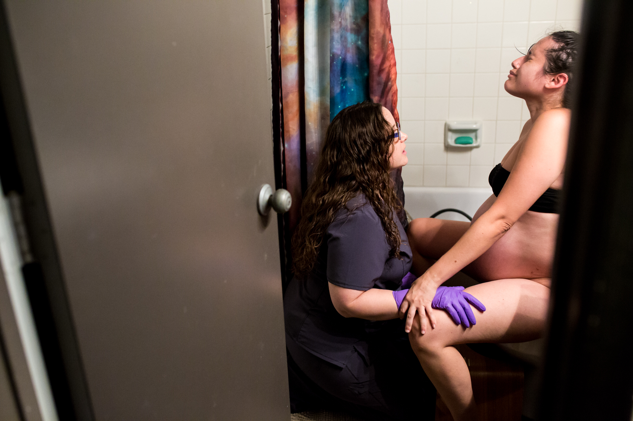 Birth Photographer Lawren Rose Photography captures a moment between a laboring mom and her midwife in the bathroom on the toilet as she powers through her final contractions in carrollton texas
