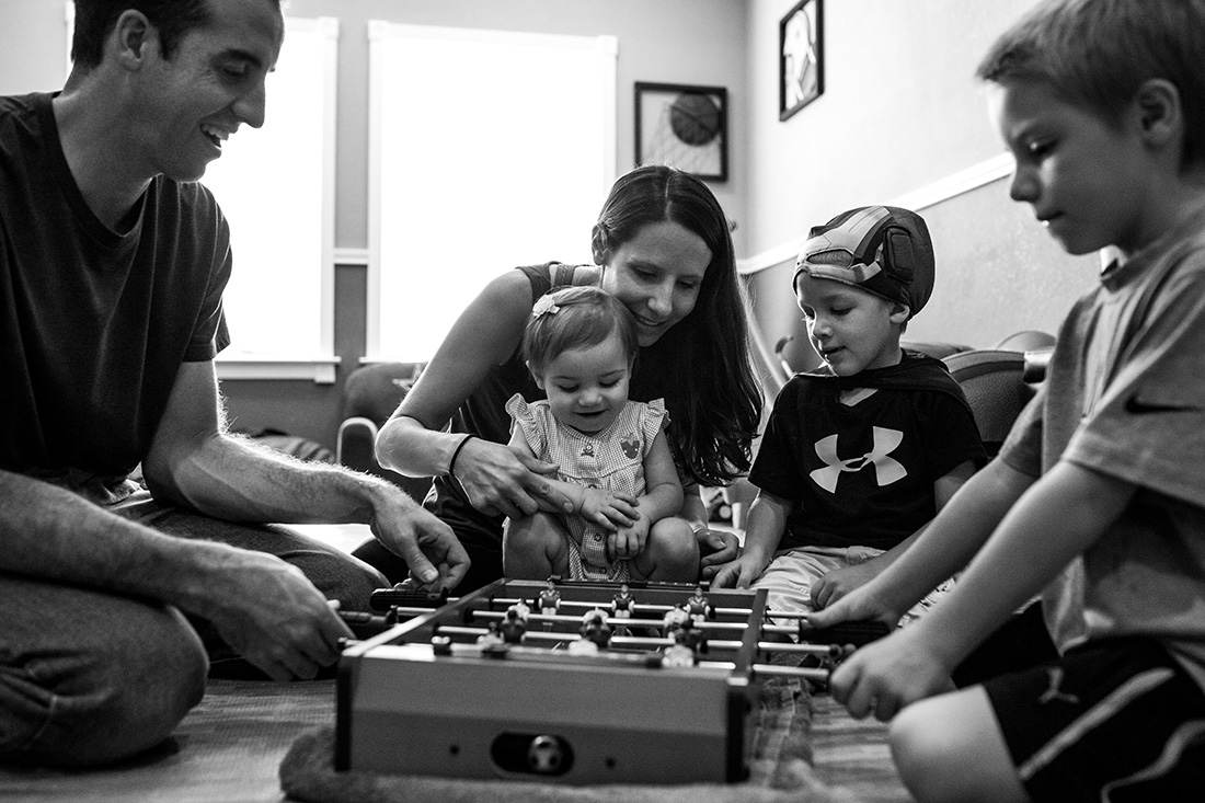 Lawren Rose Photography captures a sweet moment with a family of 5 playing a game together in a Farmers Branch in-home family session