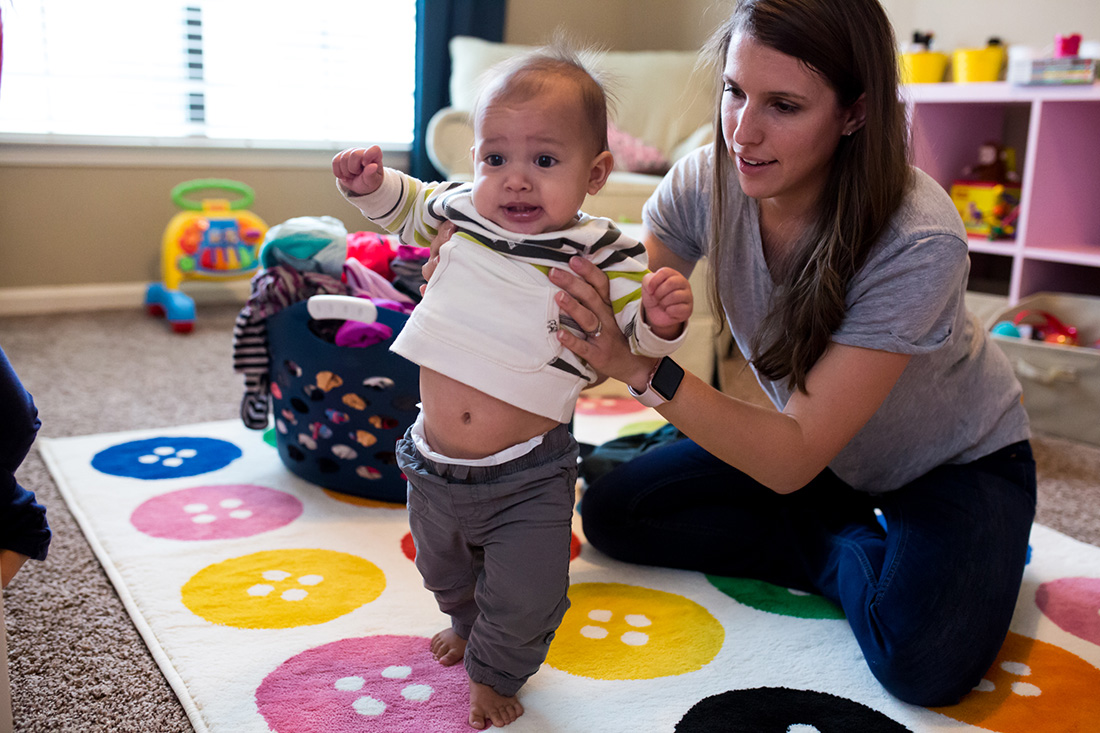 Lawren Rose Photography, a documentary family photographer, takes a picture of a Mom helping her 1 year old son walk in a Frisco, Texas home