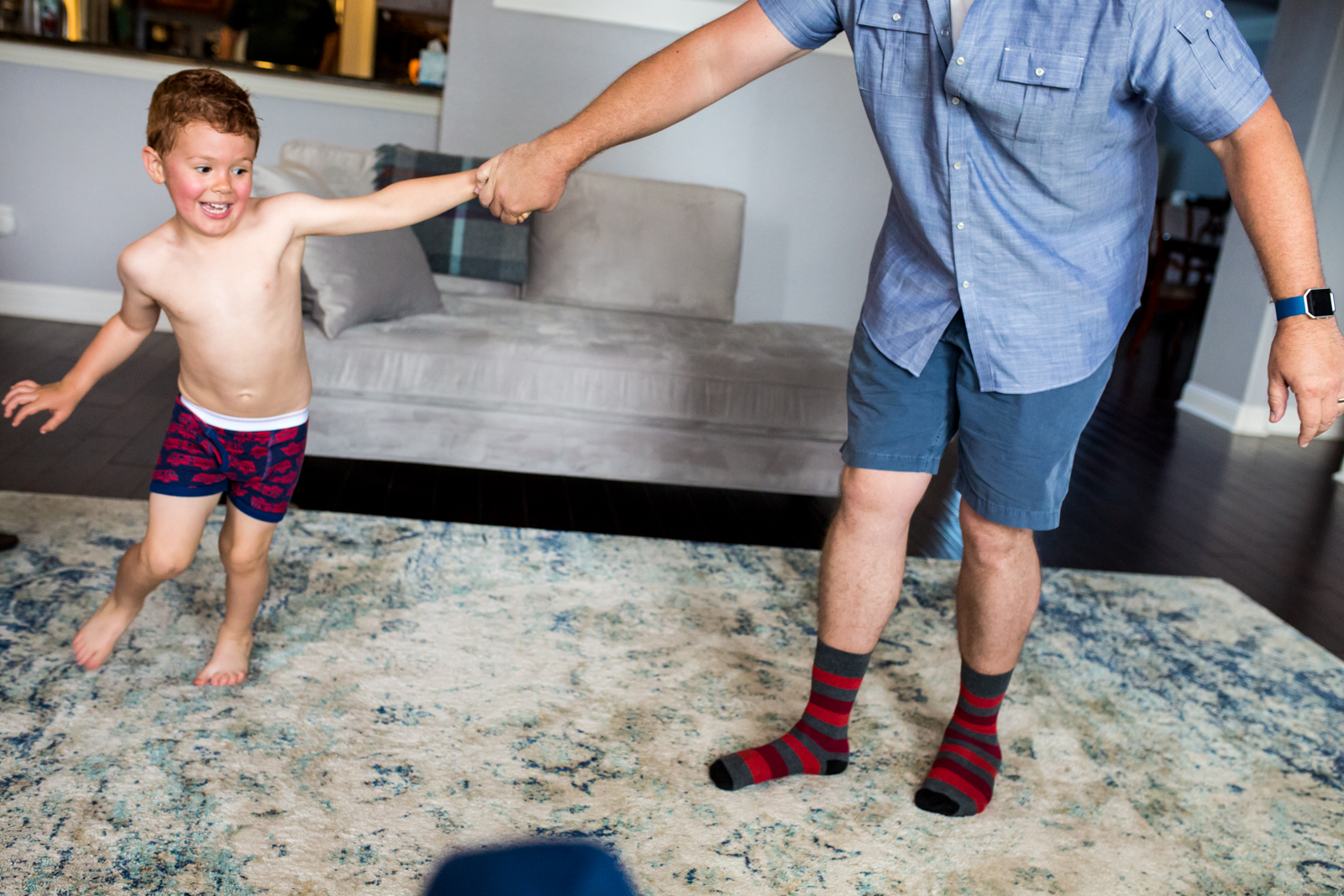 Lawren Rose Photography takes a quick photograph of a father and his son having a dance party in the living room during a maternity session in McKinney