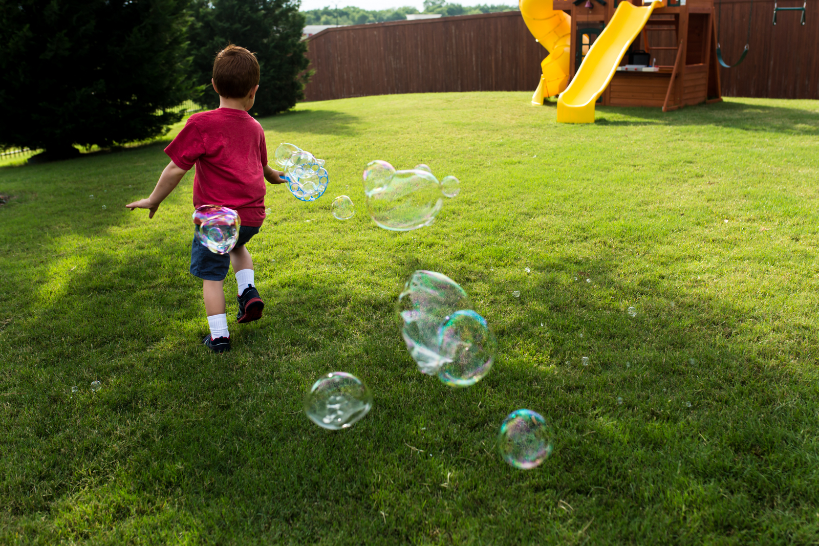 Lawren Rose Photography captures a photo of a red headed little boy running in the bright green grass with giant bubbles flowing behind him in McKinney Texas