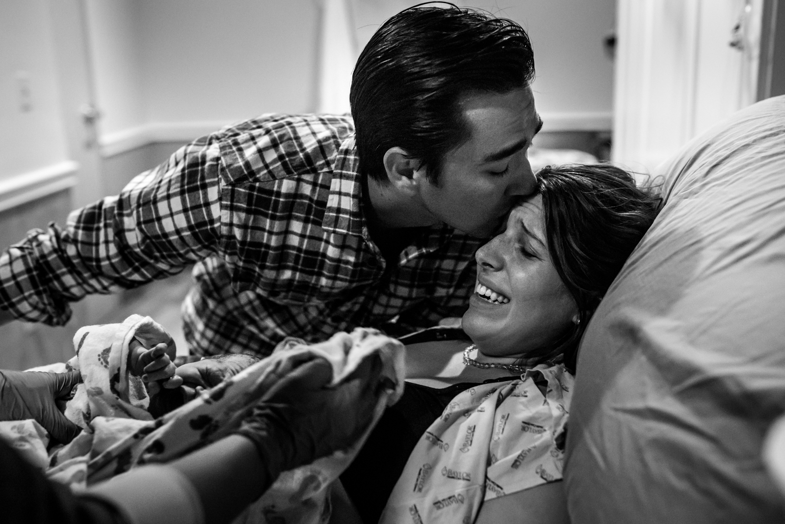 Dallas Birth Photographer Lawren Rose Photography takes an incredible photograph of a Mom holding her baby for the first time and crying while her husband kisses her forehead at Baylor University Medical Center