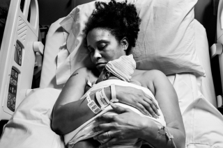 A unique photograph taken by Lawren Rose Photography of a Mother settling down with her new baby girl after 40 hours of labor, at Baylor Scott & White Medical Center - Centennial in frisco texas