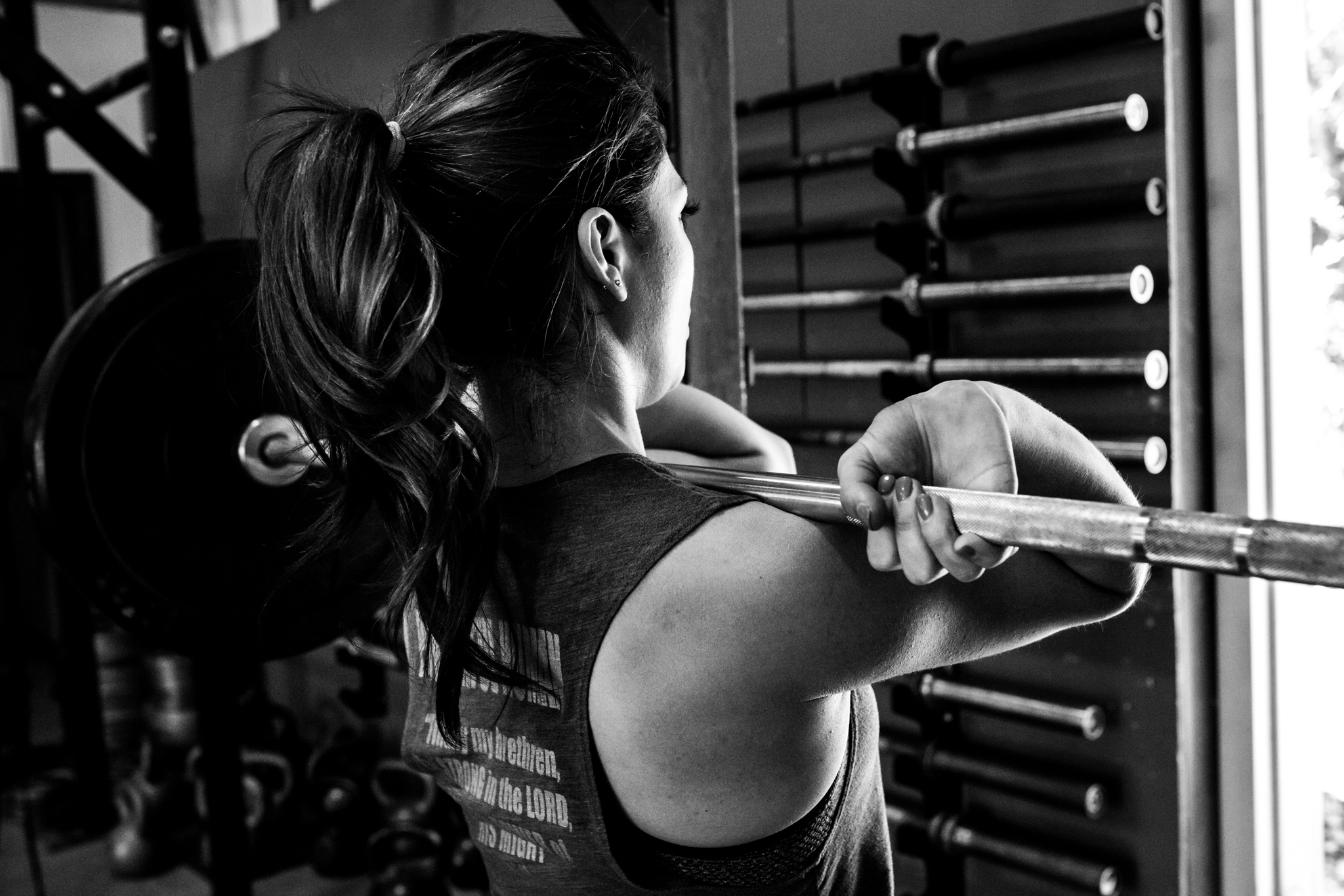 Dallas Business Photographer takes a photograph of a woman lifting a heavy barbell in the front squat position at a local crossfit gym in aubrey texas