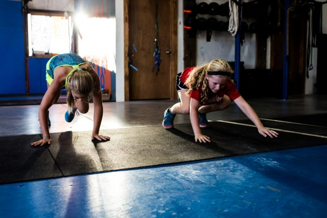 Lawren rose Photography quickly catches a still photo of two young girls doing inch worms at a local crossfit gym in aubrey texas