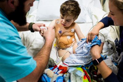 Lawren Rose Photography takes a very personal photograph of a little boy coming out of surgery hooked up to a bunch of wires sitting in bed in dallas texas at the childrens hospital
