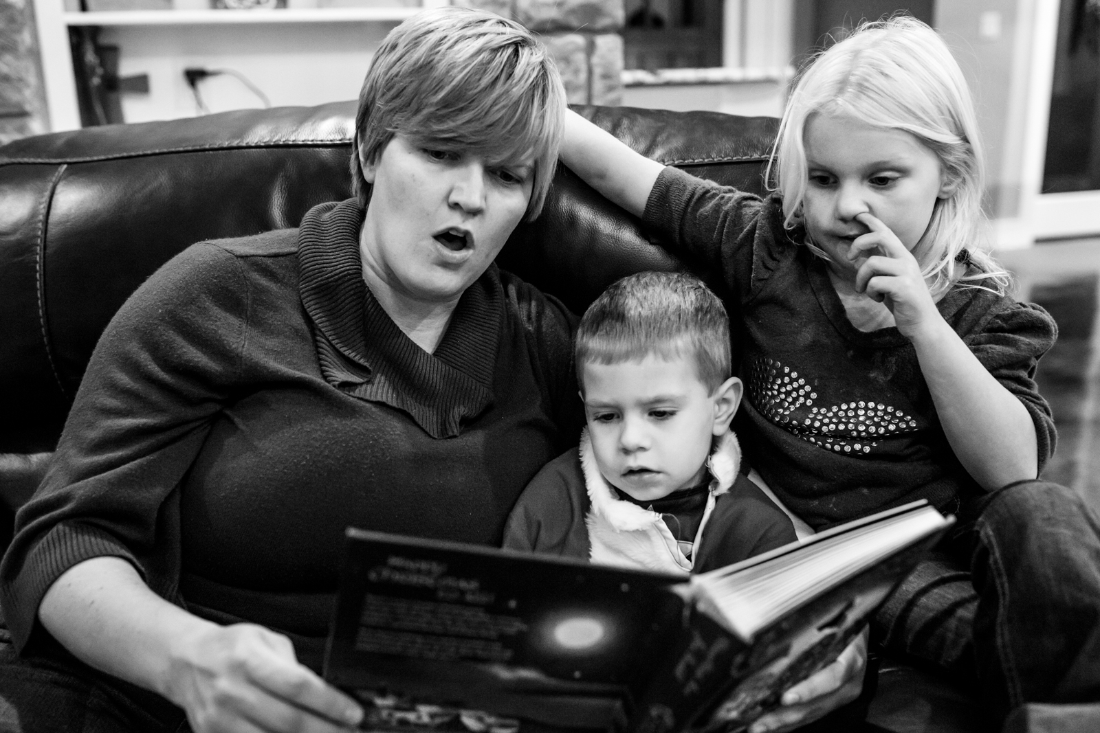 Documentary photographer Lawren Rose Photography takes a photo of a family of 3 sitting and reading a book while one child picks her nose