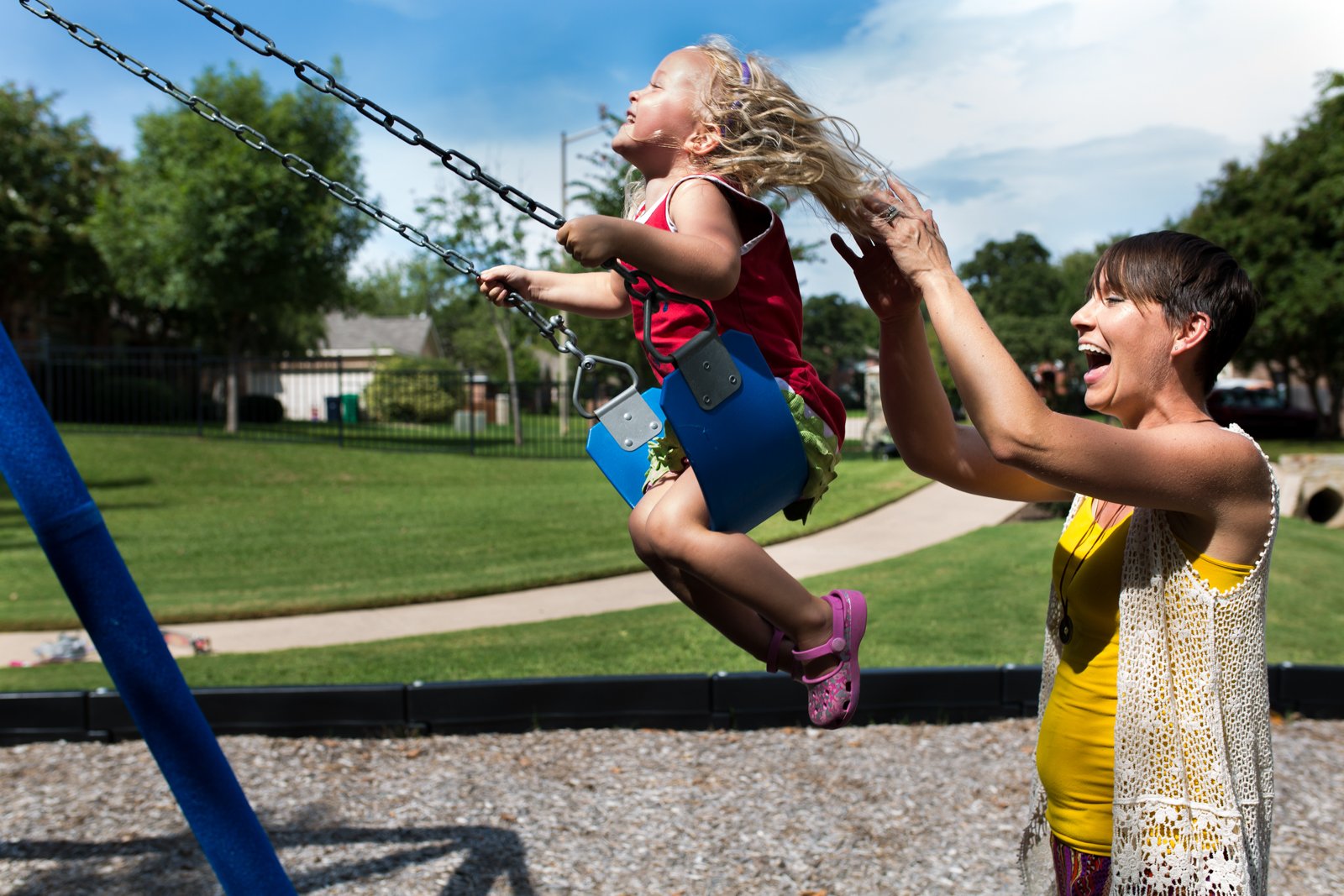 Lawren Rose Photography captures a bright photo of a mom pushing her daughter on a swing set in Denton Texas