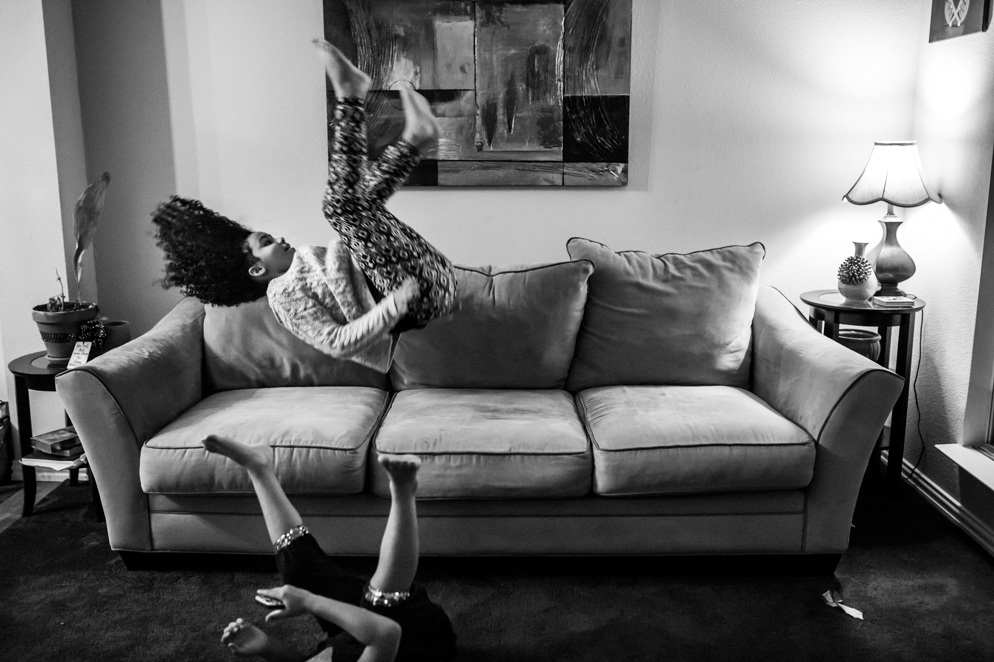 Documentary photographer Lawren Rose Photography takes a picture of a pre teen doing flips on the couch