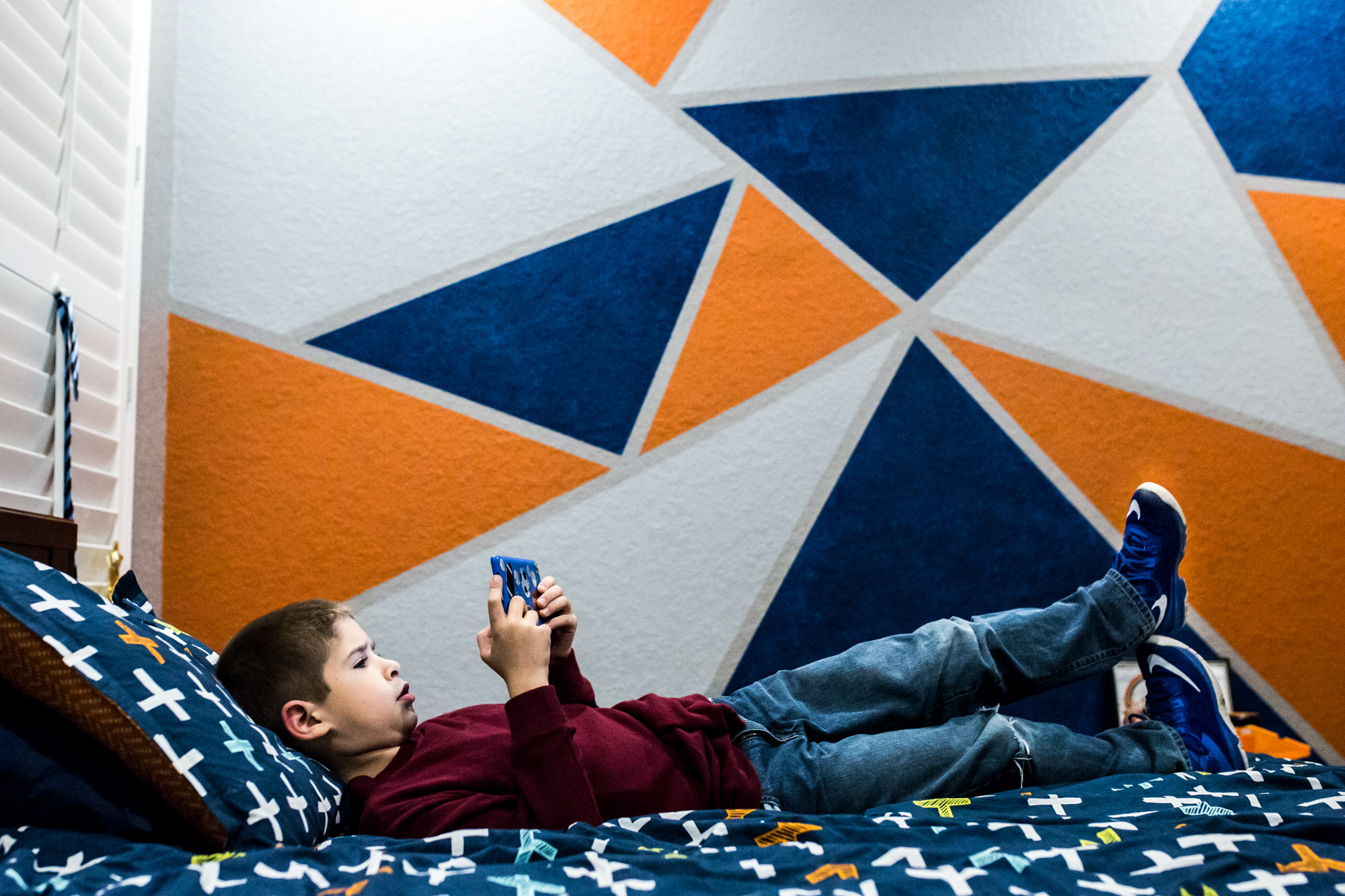 Lawren Rose Photography takes an environmental portrait of a young boy in his room playing a video game