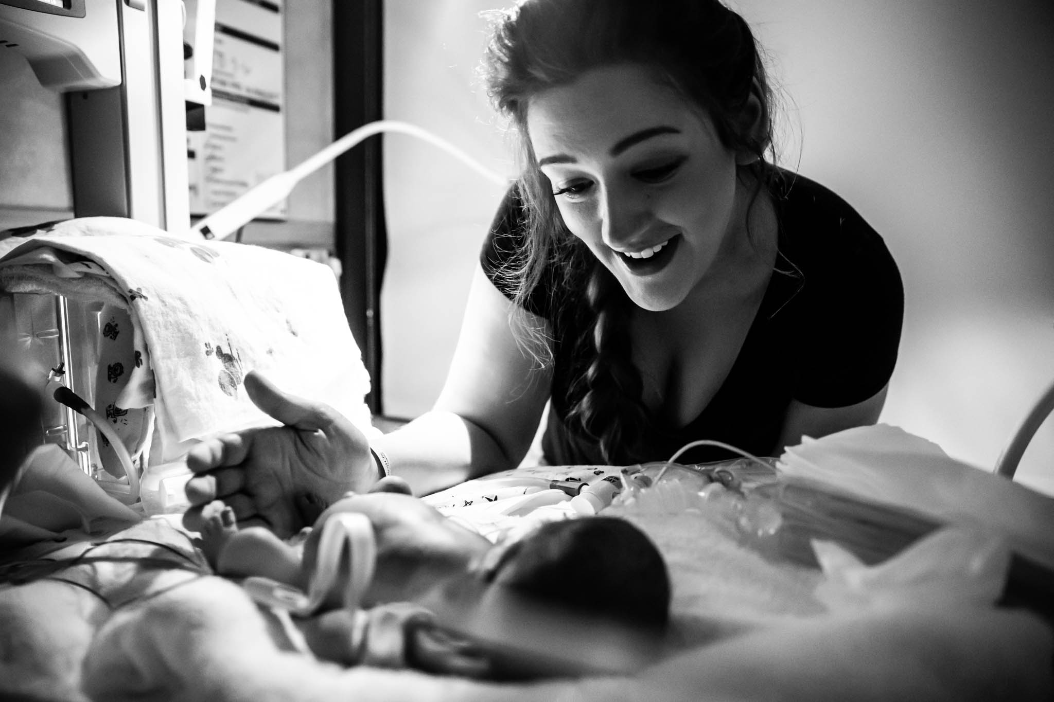 Lawren Rose Photography takes a picture of moms face when she bathes her nicu micro preemie for the first time