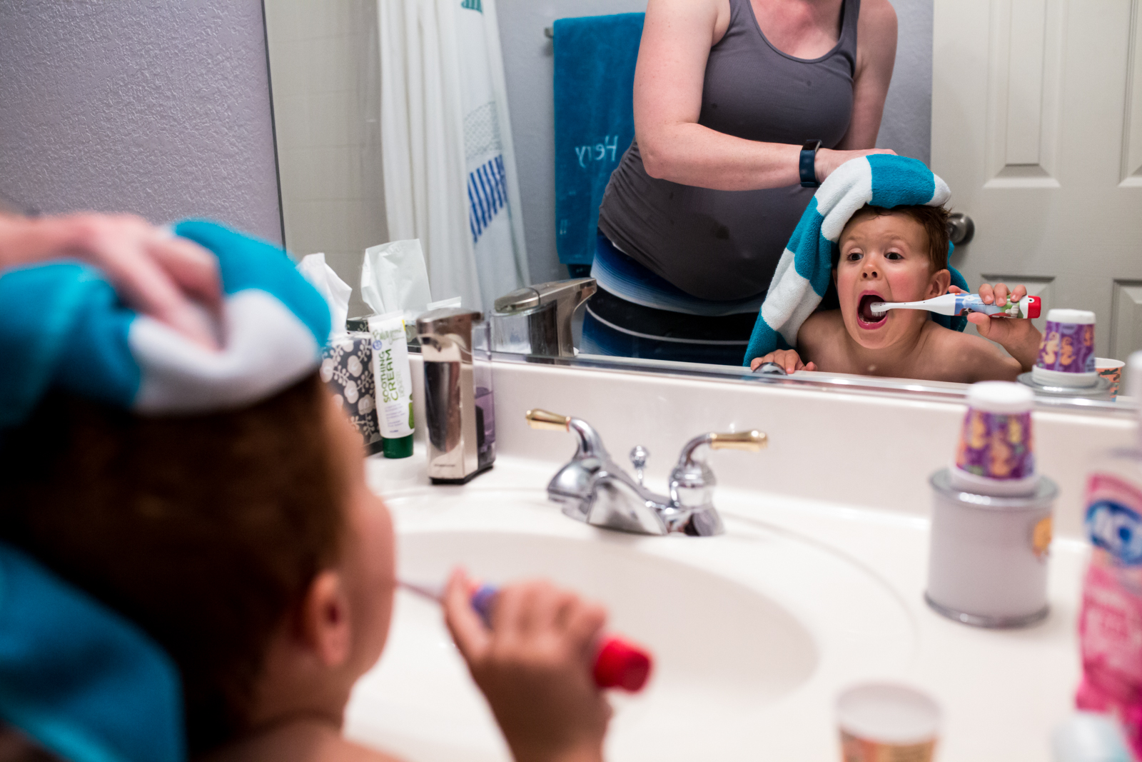 Little boy makes a goofy face in the mirror while his mom tries to dry off his hair after a bath, photo taken by Lawren Rose Photography in McKinney Texas