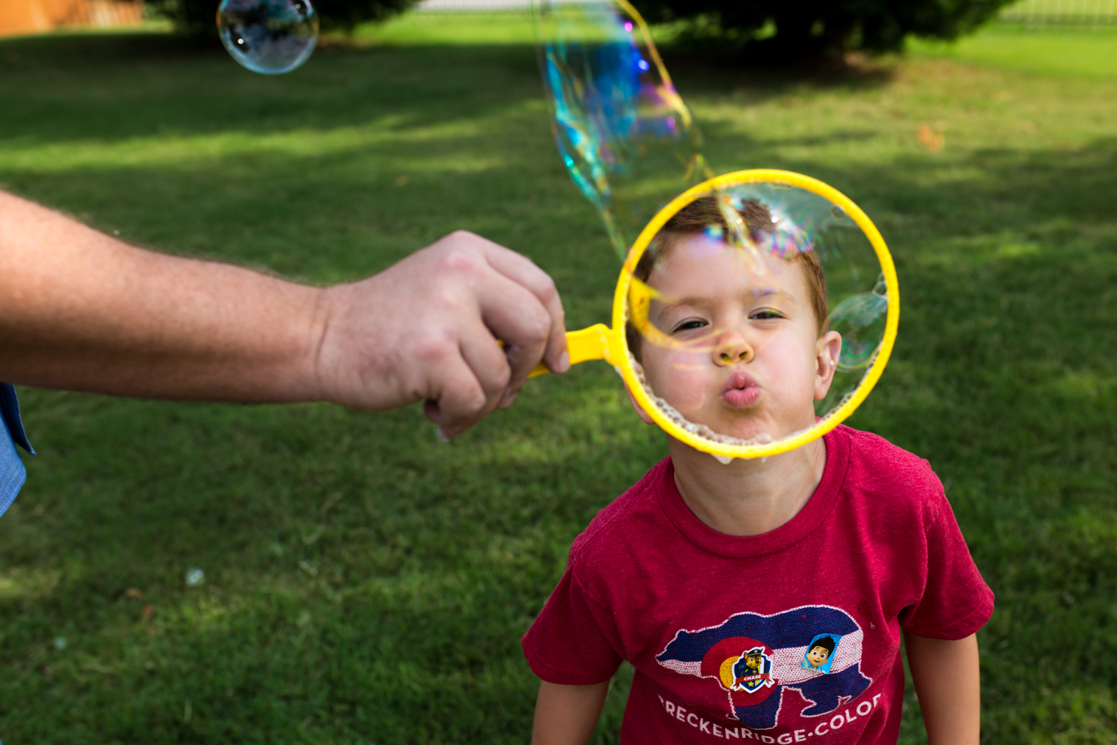 Maternity Photographer Lawren Rose Photography takes a photo of a red headed boys face while he is blowing a giant bubble in McKinney Texas