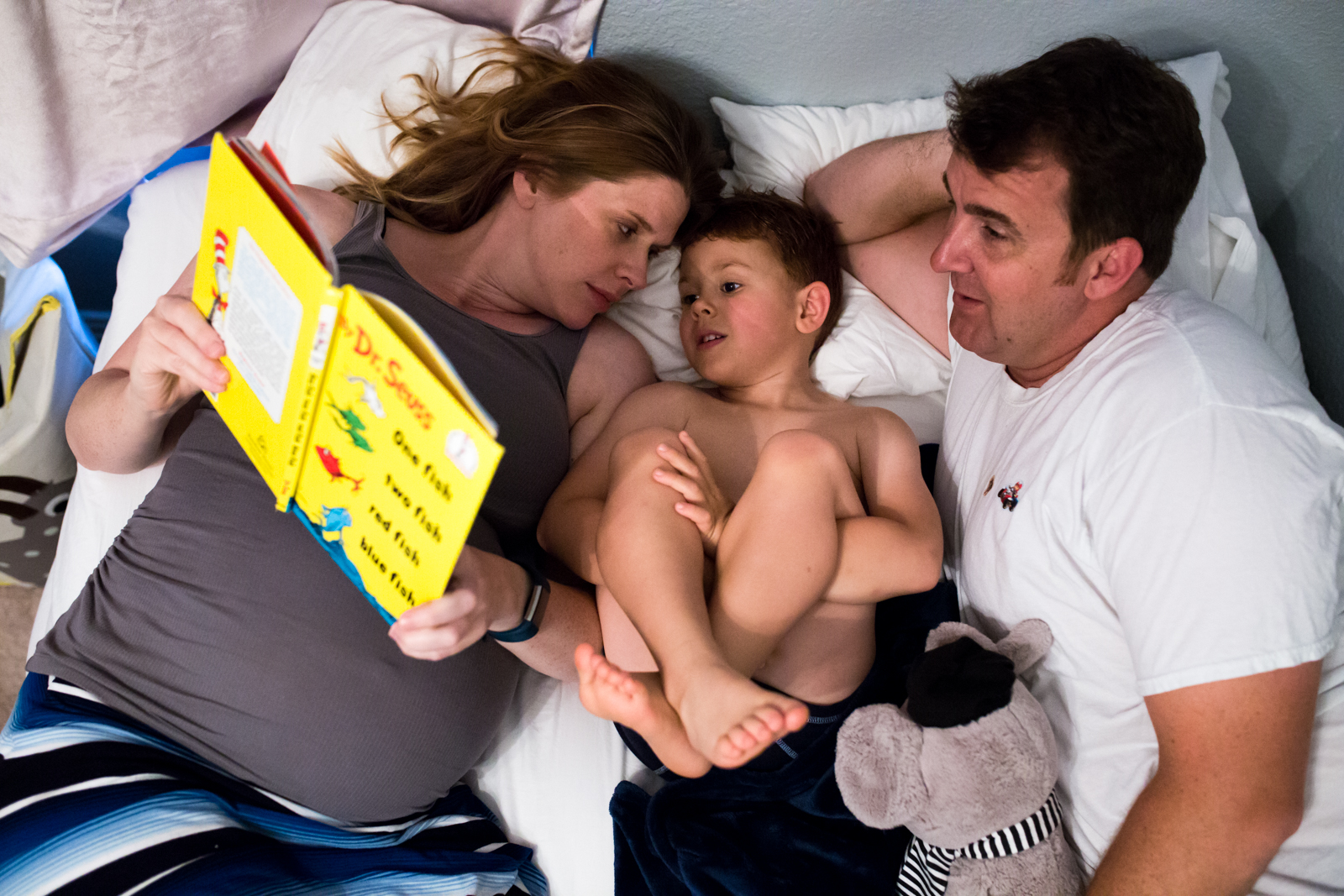 Maternity Photographer Lawren Rose Photography takes a photo from above of a family of 3 laying in bed reading a dr. seuss book in mckinney texas