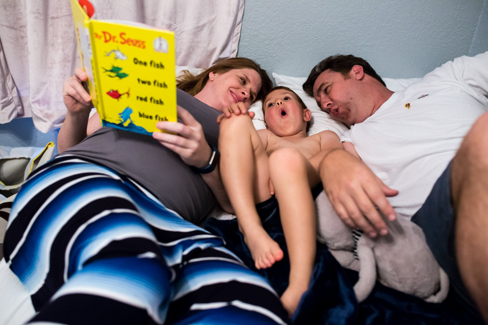 Maternity Photographer Lawren Rose Photography takes a photo of a family acting out a dr seuss book laying in bed in mckinney texas