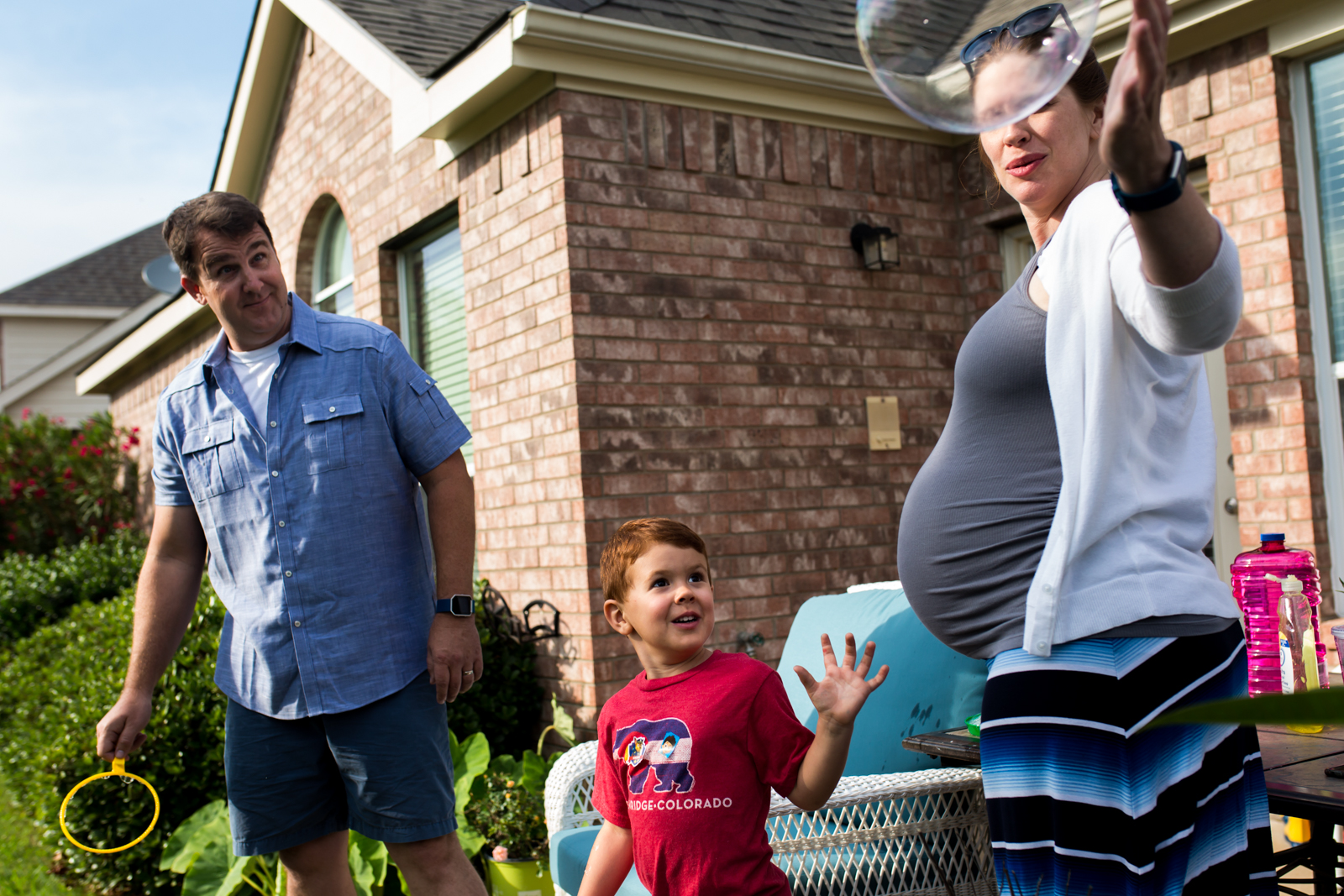 McKinney Photographer Lawren Rose Photography captures a photo of a family of 3 outside in their backyard blowing giant bubbles