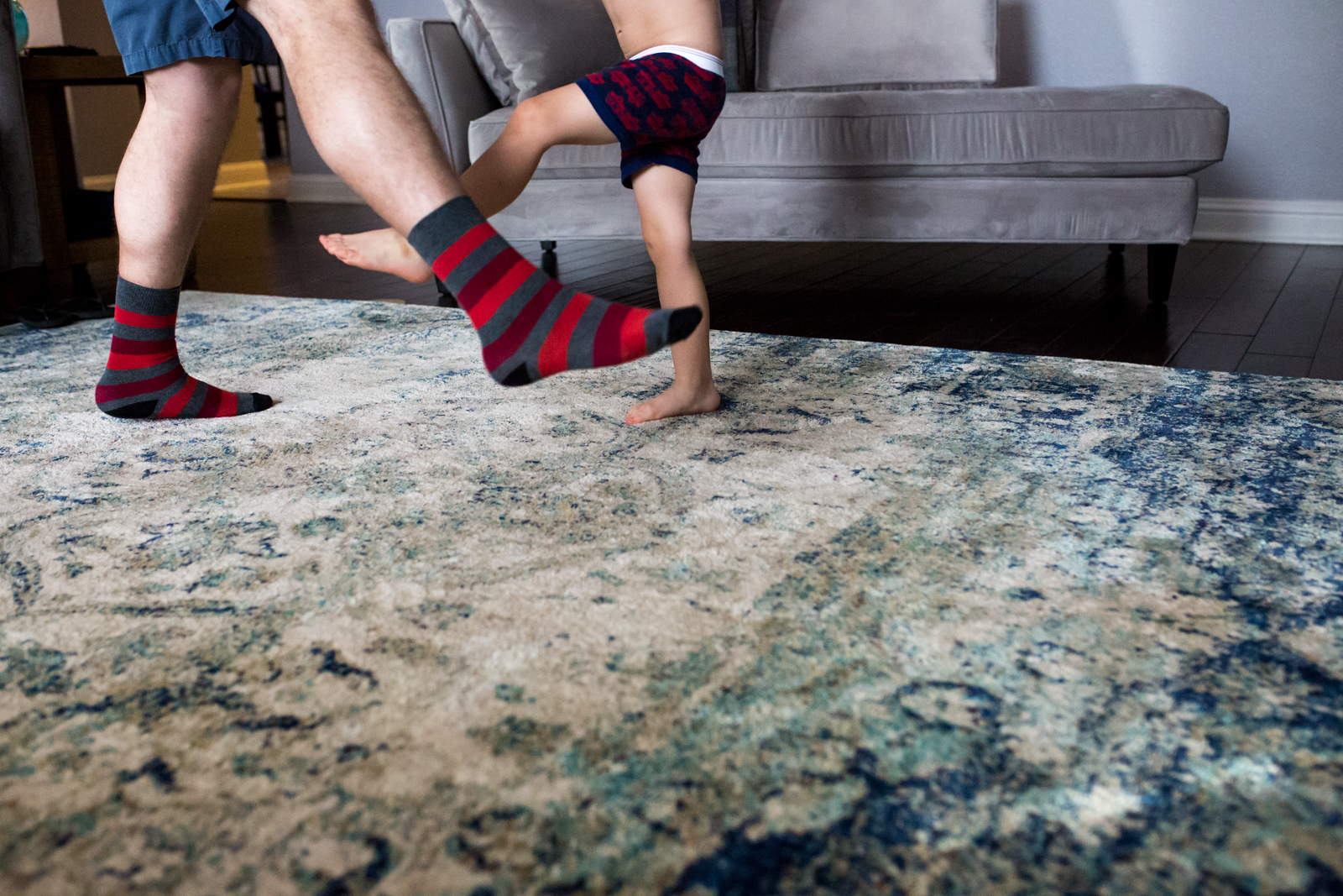 Lawren Rose Photography takes a minimalist photo of a dad and son dancing where dad is wearing funky socks on the living room floor in mckinney texas