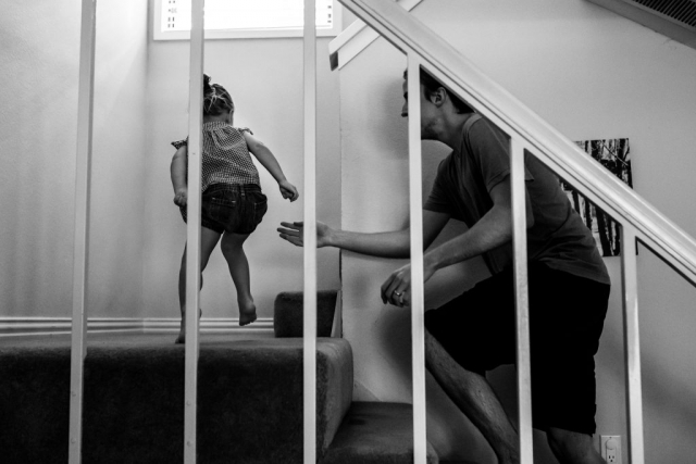 During an in-home family session, Lawren Rose Photography quickly captures a father running after his daughter upstairs playing in dallas texas