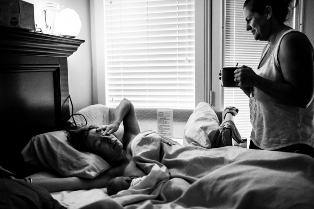 Lawren Rose Photography captures a very unique photograph of a Mom giving a cup of warm tea to her daughter in bed who just had a baby 3 days ago, right when she wakes up in farmers branch texas