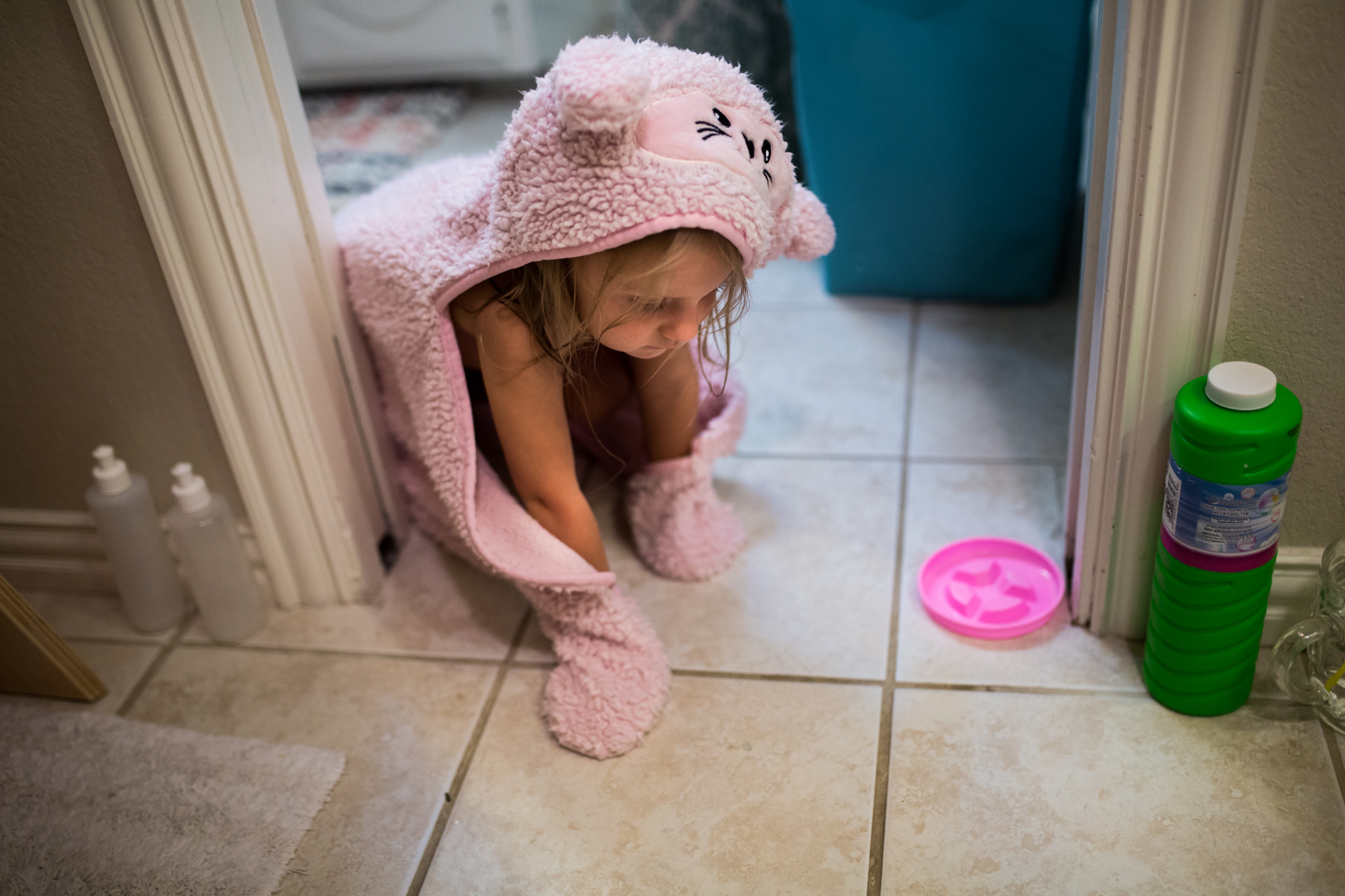 Lawren Rose Photography takes a picture of a little girl crawling on the floor wearing a cat towel pretending to be a cat during an in-home family session in farmers branch texas