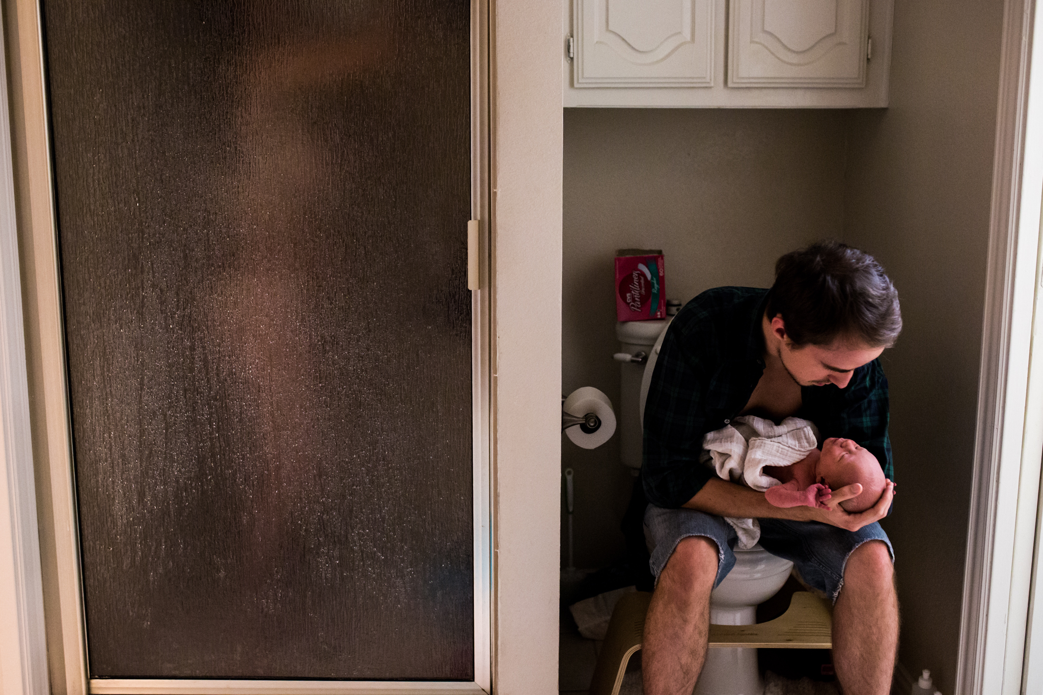 Lawren Rose Photography, a dallas documentary family photographer, snaps an intimate photo of a new mom taking a shower while dad sits nearby on the toilet holding their 3 day old son in an in-home session in farmers branch, texas
