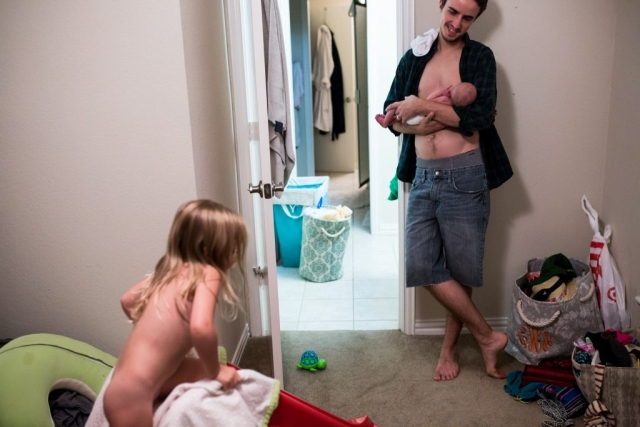 documentary photographer, Lawren Rose Photography, captures an image of a dad holding his newborn baby boy watching his daughter play on the slide naked at the end of an exhausting day