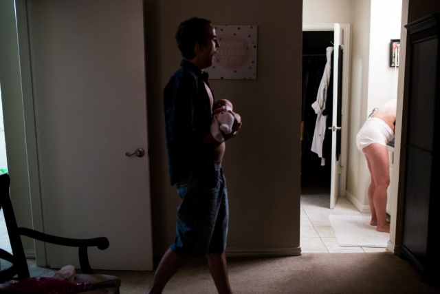 Lawren Rose Photography captures a real moment during a Day In The Life family session in farmers branch texas, of a father holding his 3 day old son yawning from exhaustion while walking to the bathroom where you can see the new mom bending over the sink wearing depends