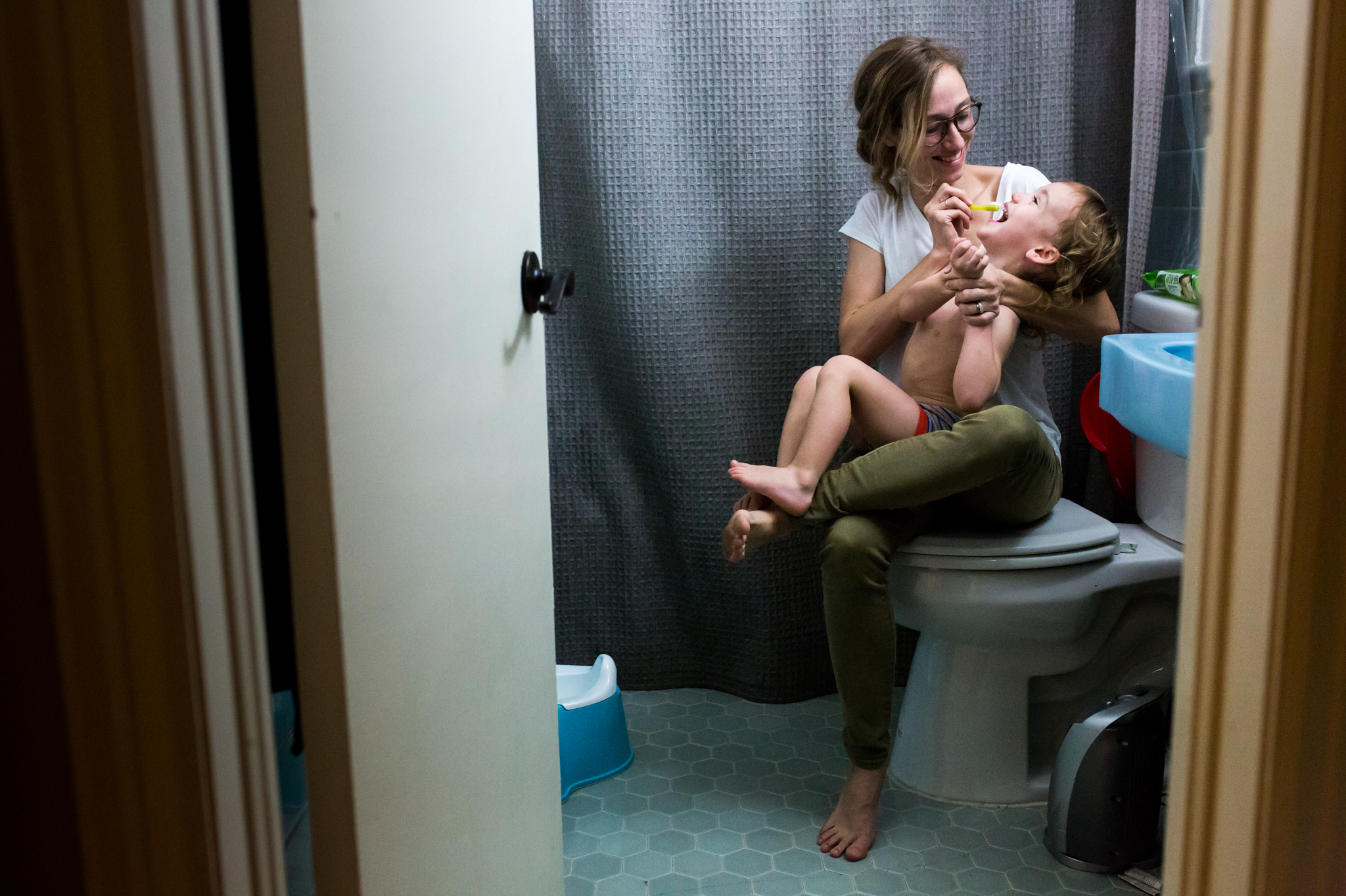 Lawren Rose Photography, a dallas family photojournalist, takes a photograph of a Mom trying to brush her wild child's teeth