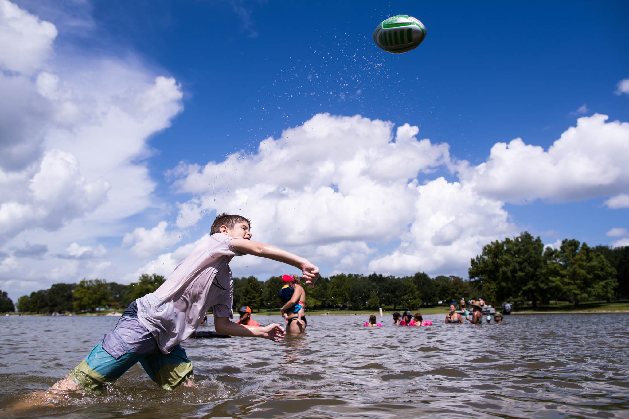 Lawren Rose Photography takes a photograph of a boy throwing a football in a lake with bright blue sky behind him