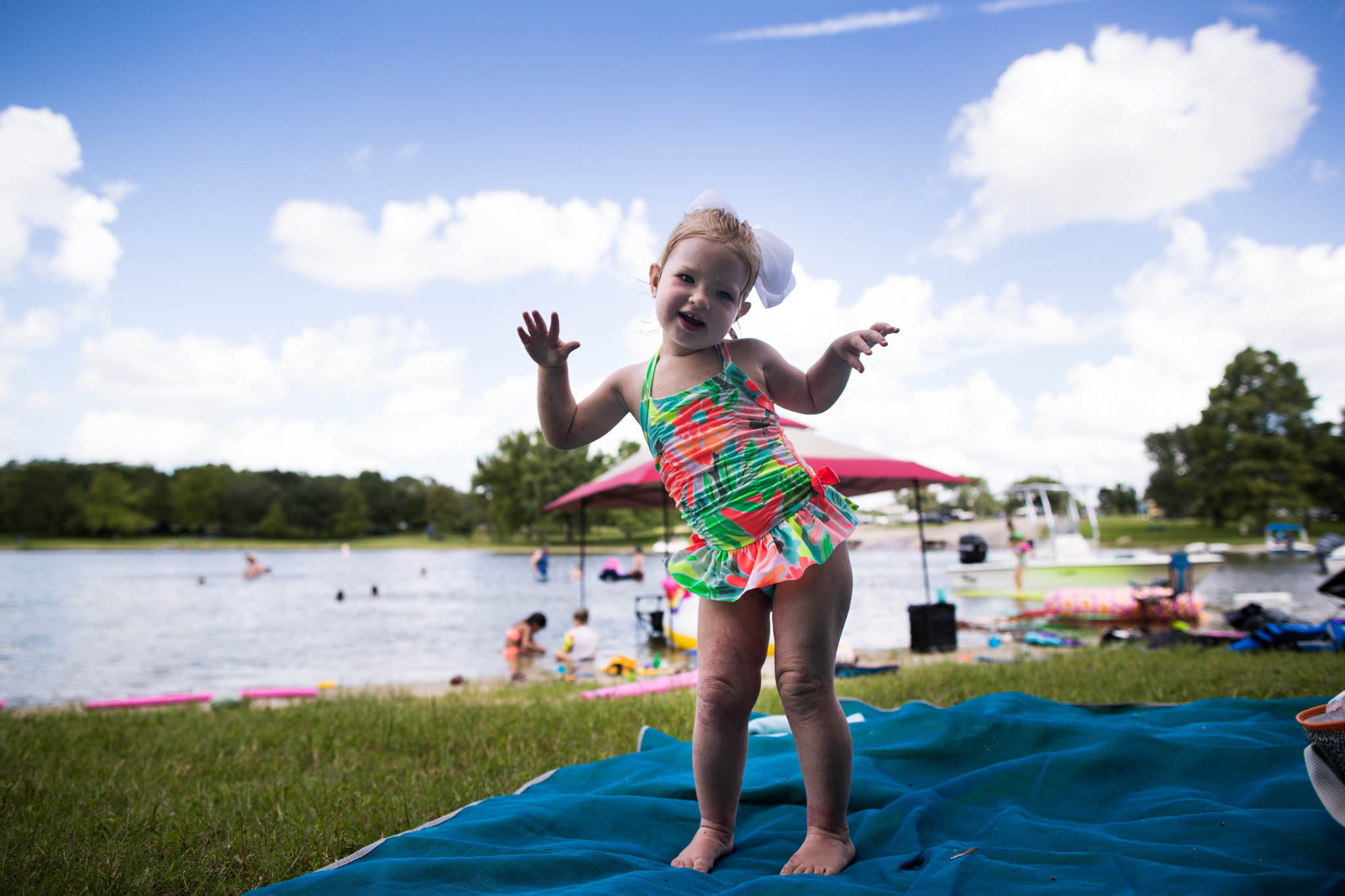 Lawren Rose Photography takes personal photos of her daughter in front of a lake in her swim suit dancing it up