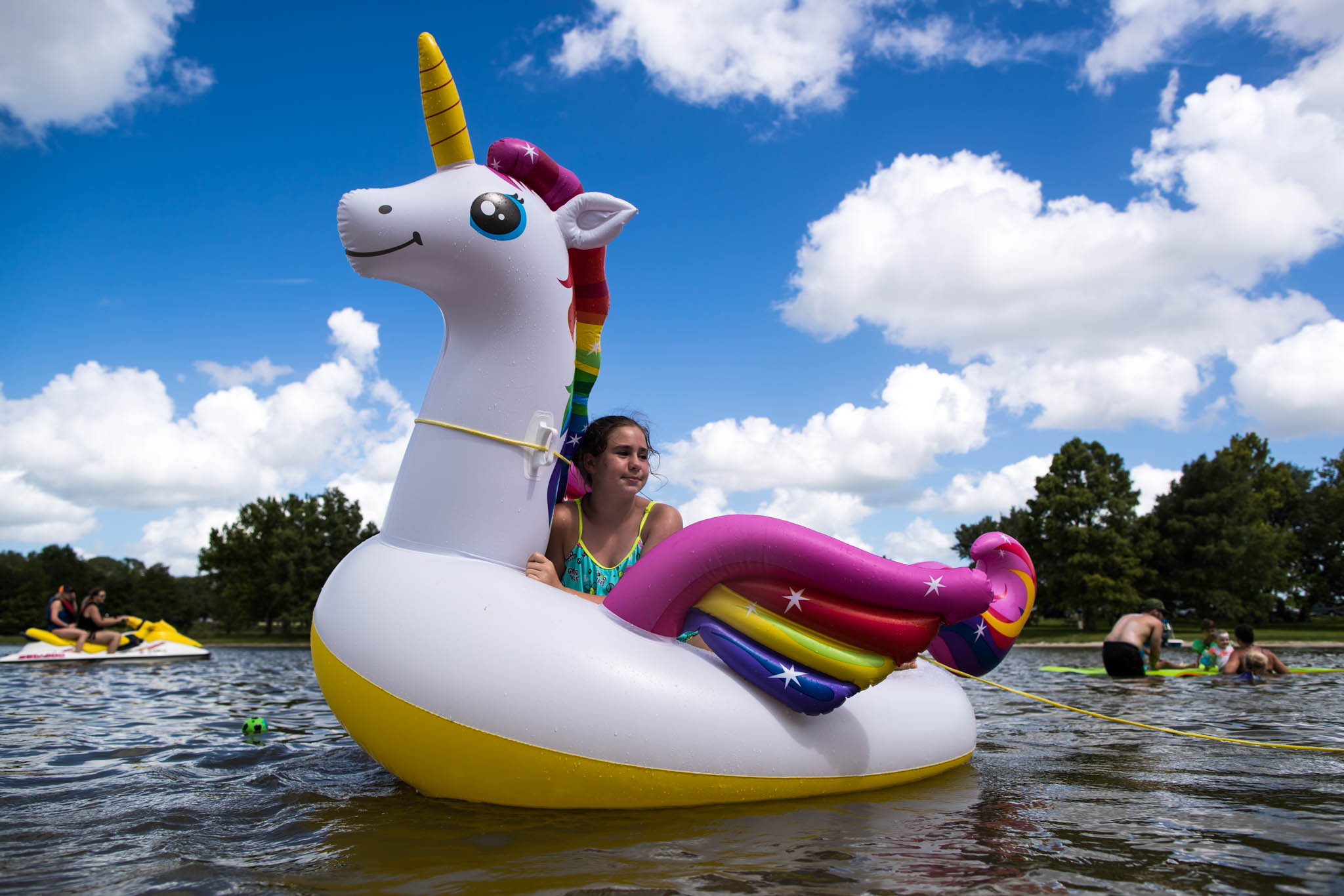Dallas Family Photographer, Lawren Rose Photography, takes an environemtal portrait of a young girl sitting on an inflatable unicorn