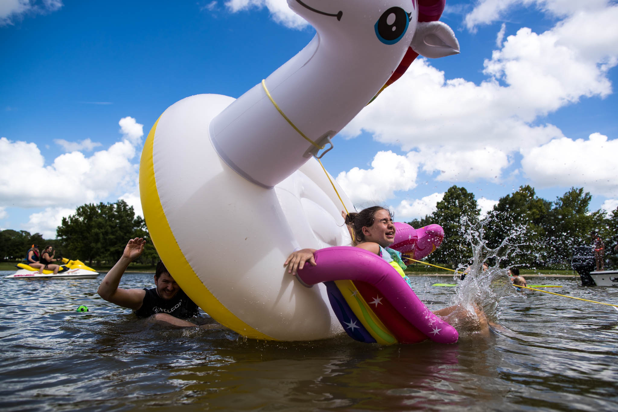 Lawren Rose Photography, a Dallas family photographer, captures a photo when someone is pushing someone else off a float in the lake
