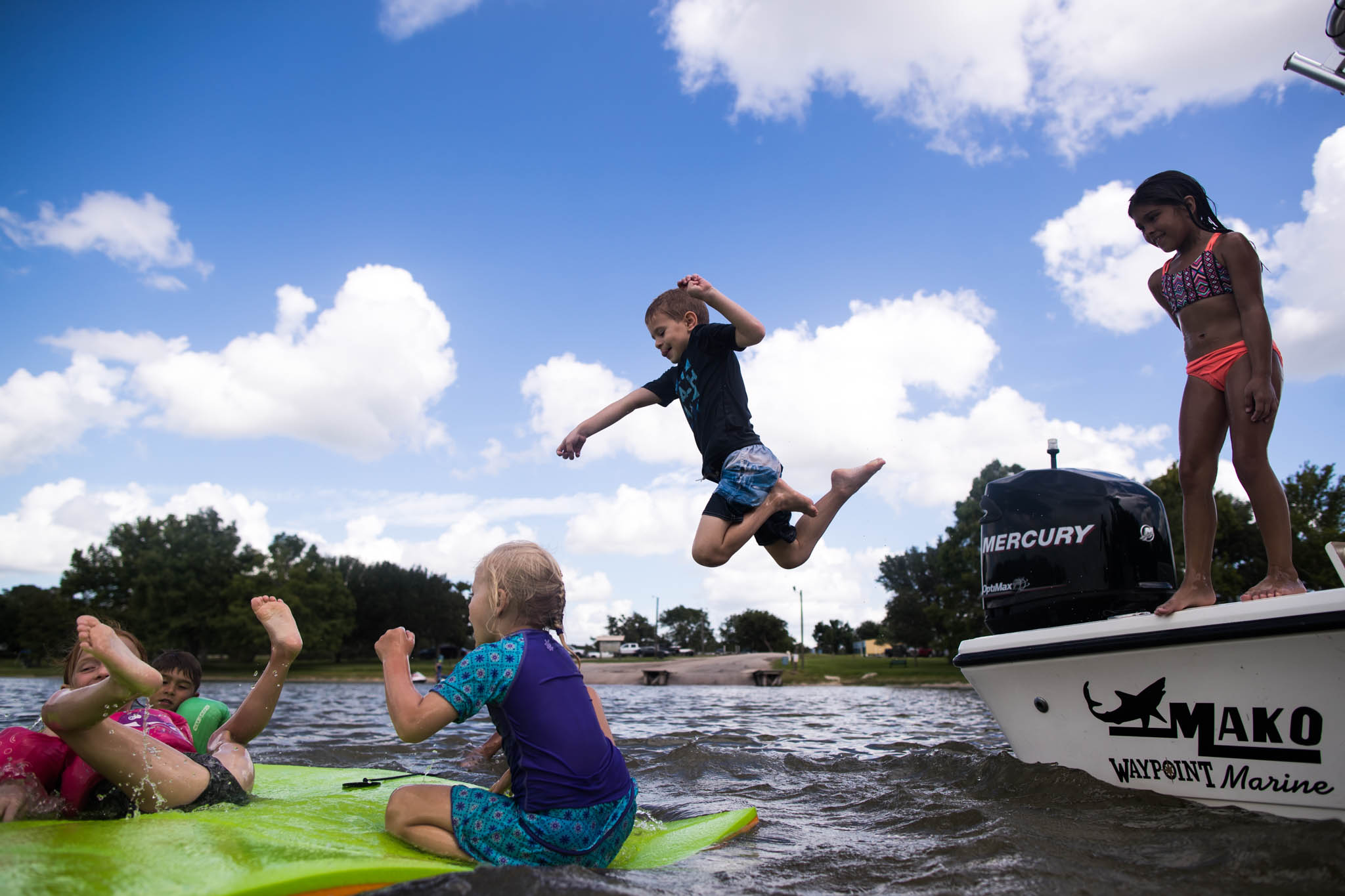 Lawren Rose Photography, a documentary family photographer, captures an image of a boy jumping very high into the lake
