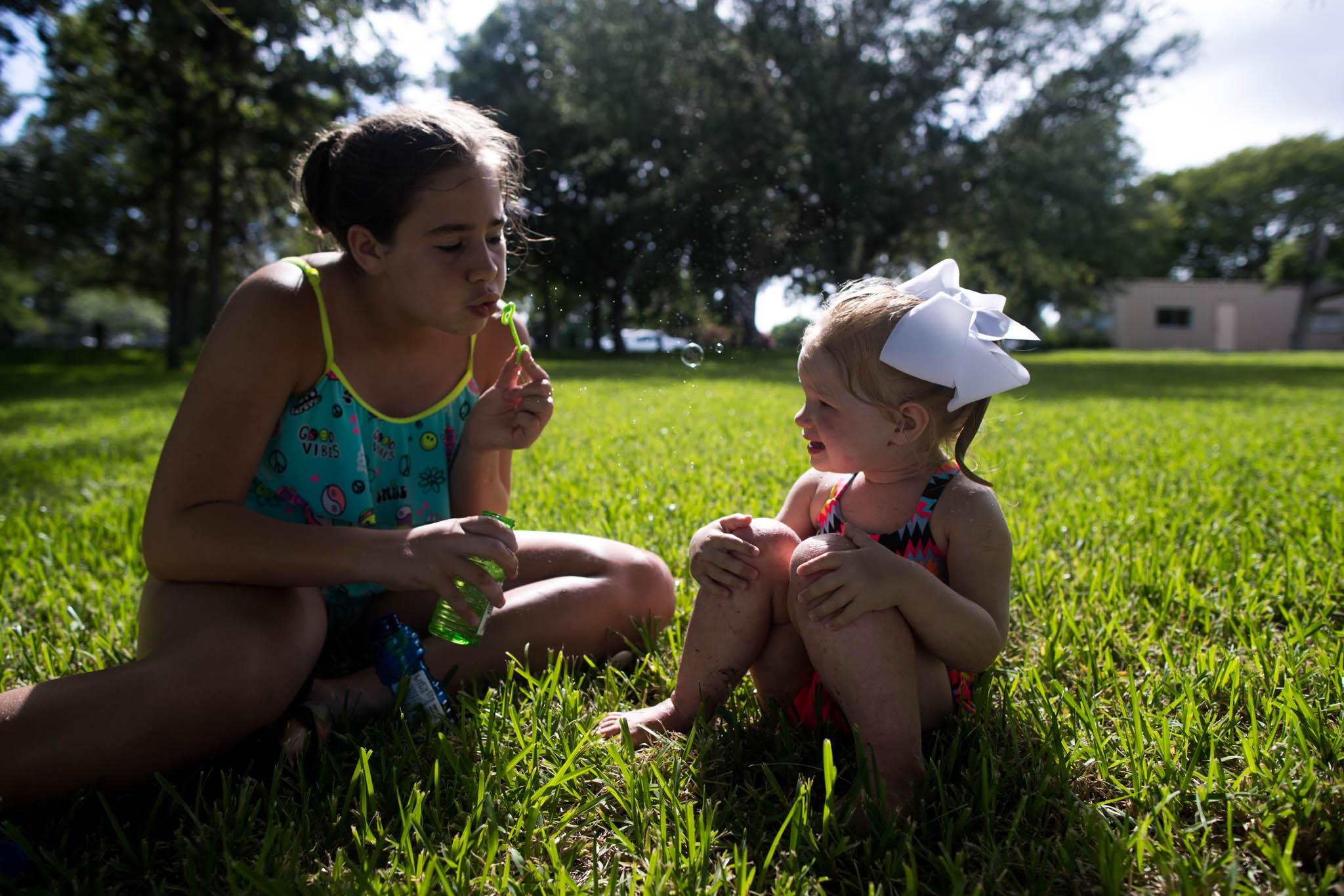 Lawren Rose Photography captures the perfect moment between two girls who are sitting in grass blowing bubbles
