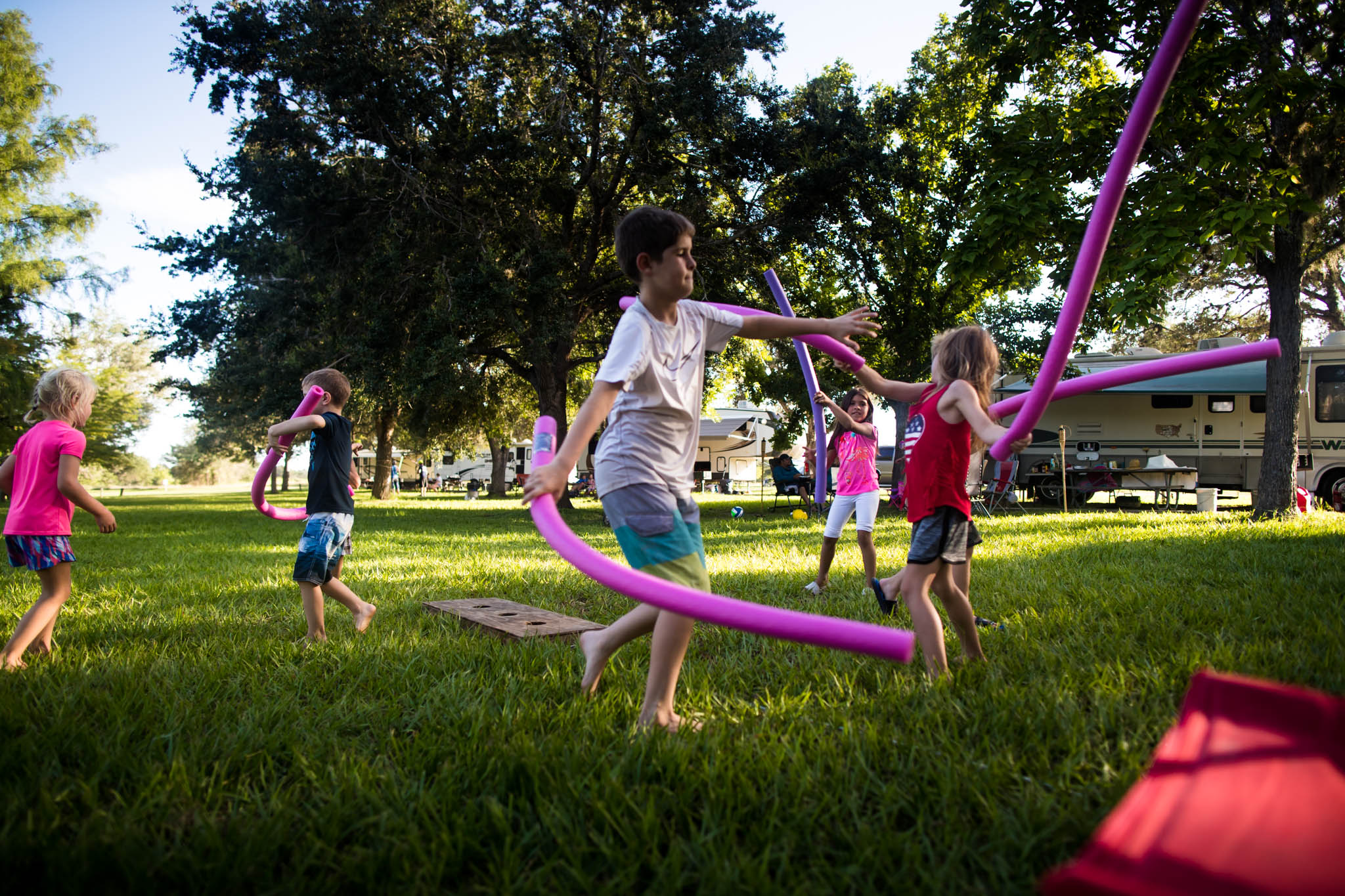 Lawren Rose Photography, a dallas family photographer, captures an image where a bunch of kids are playing and swinging pink pool noodles around