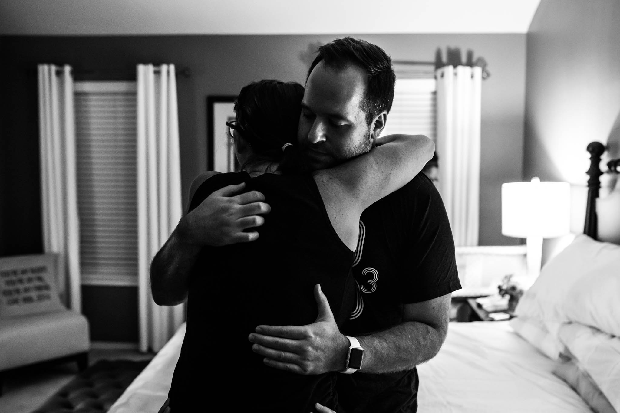 Lawren Rose Photography a birth photographer in Denton, texas takes a picture of a husband and wife hugging during labor