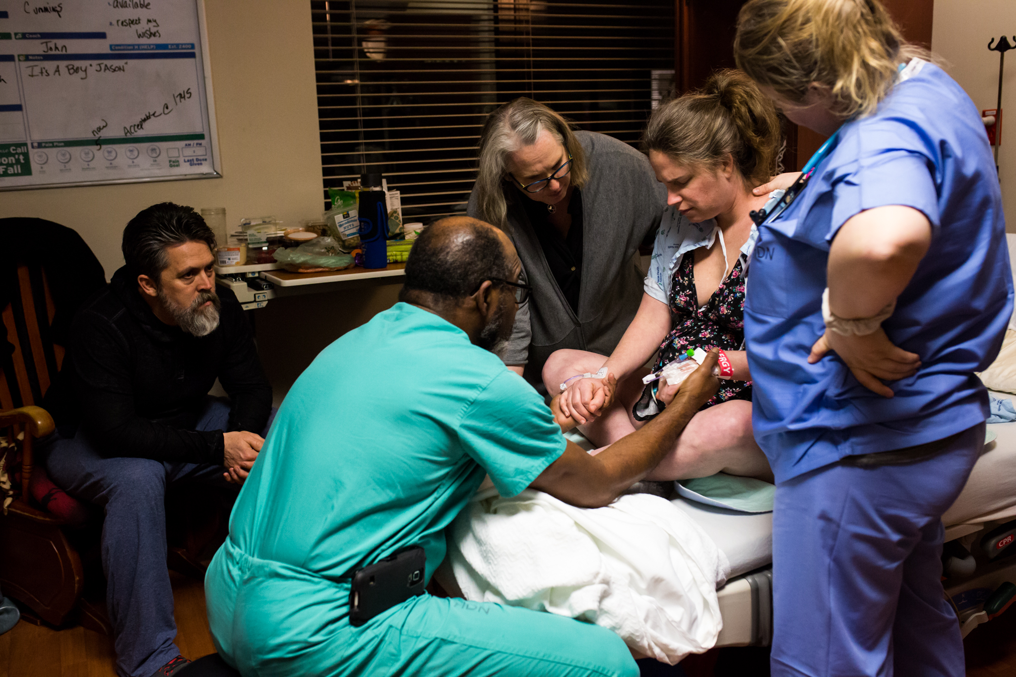 Lawren rose Photography, a dallas birth photographer, takes a picture in denton texas as dr cummings holds the hands of his patient in labor