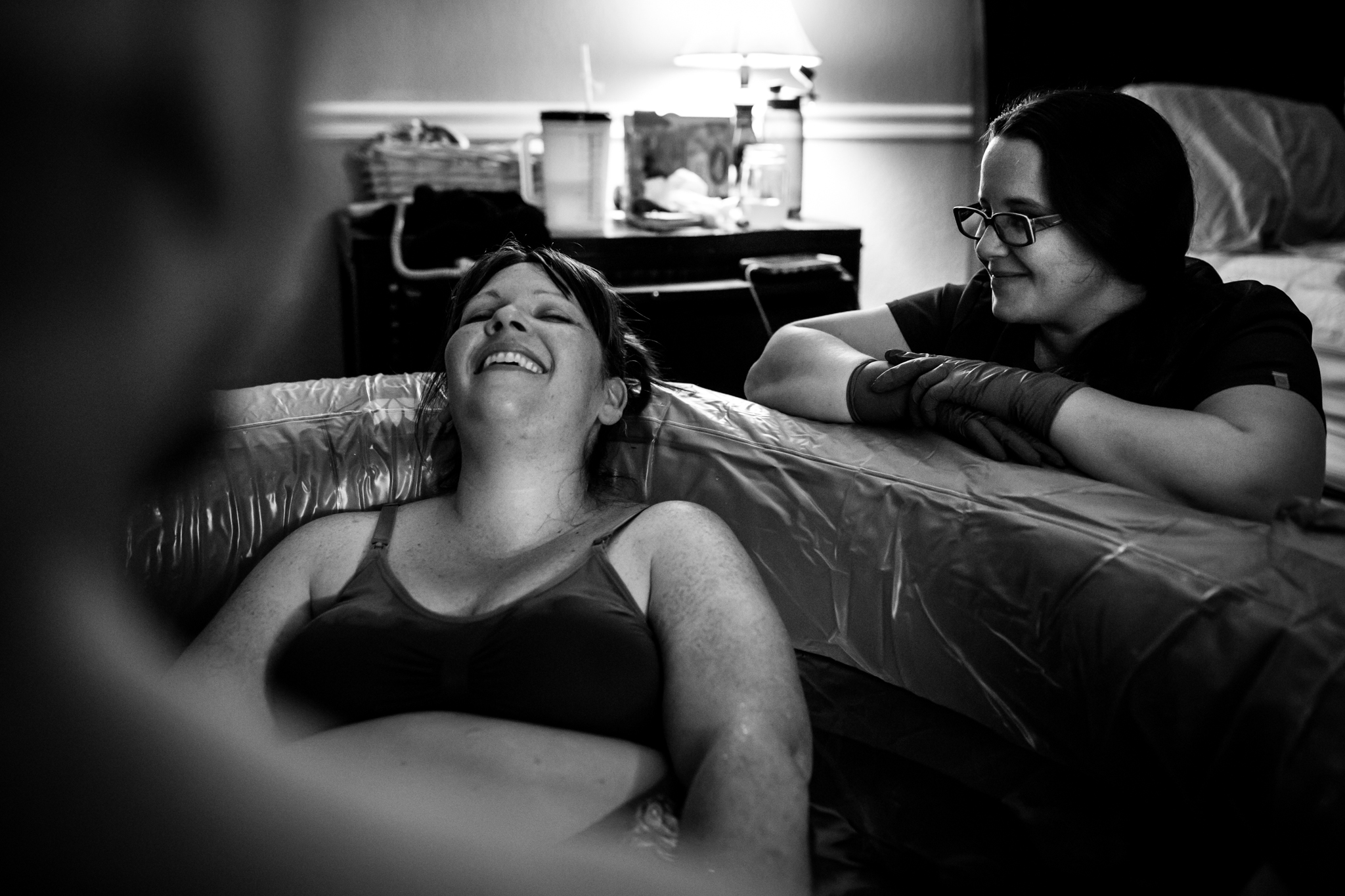 Lawren Rose Photography, a dfw birth photographer, takes a photo of a mother laughing during labor during a home birth in flower mound texas