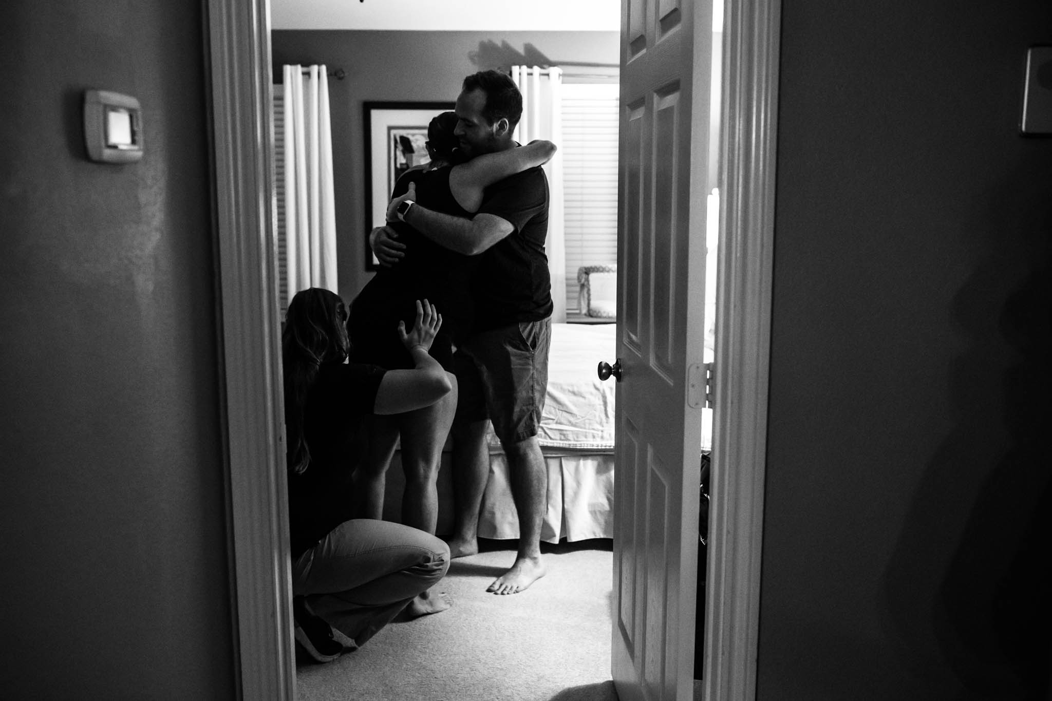 Lawren Rose Photography, a denton birth photographer takes an image peeking into a room where a mom is laboring holding onto her husband and doula applying counter pressure