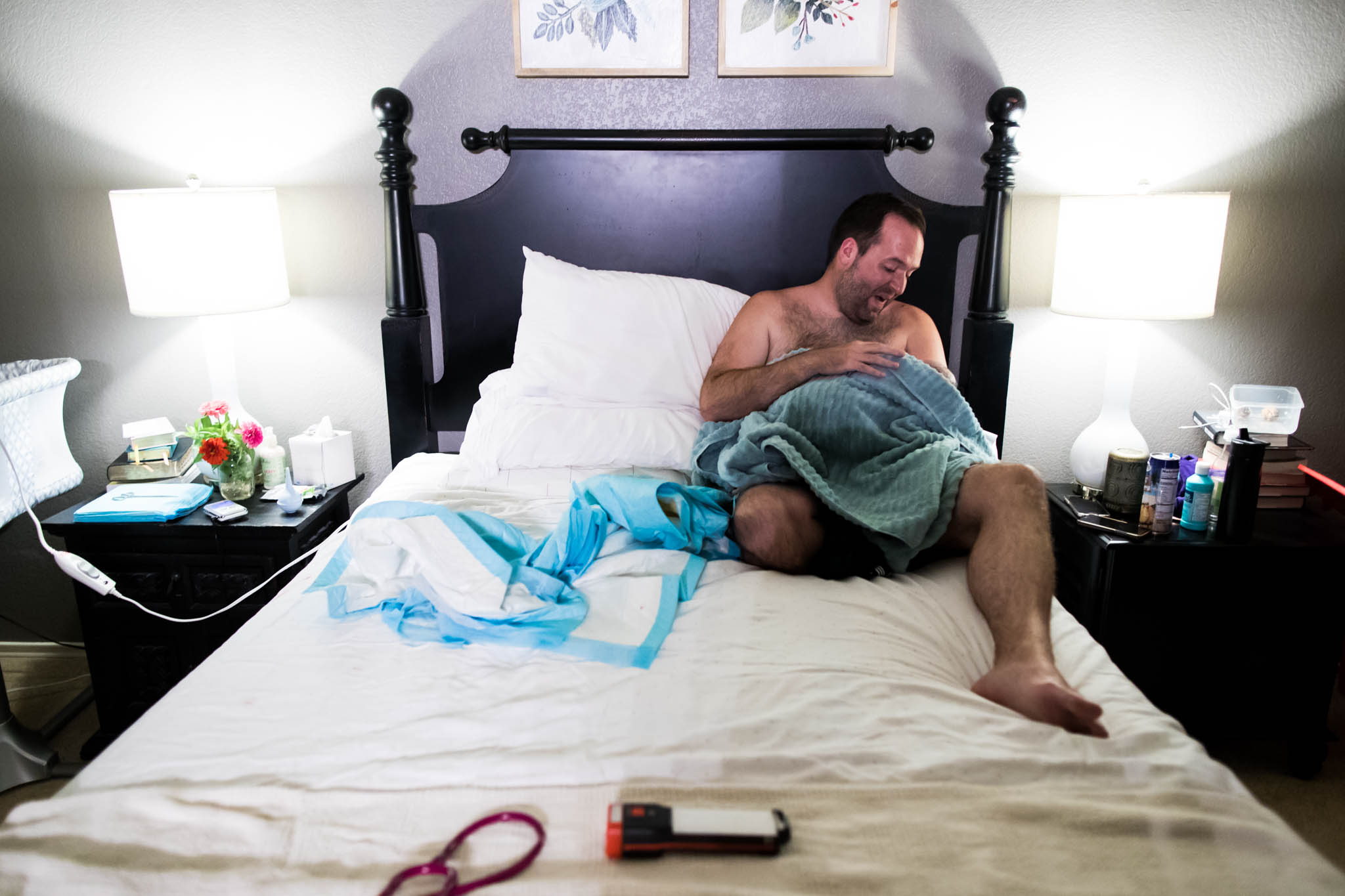 During a denton texas home birth, photographer Lawren Rose Photography captures an image at a distance of a new Dad sitting on his bed gazing at his new son