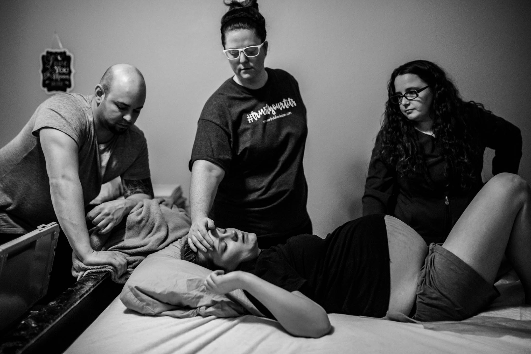 Lawren Rose Photography, a little elm birth photographer, takes an image as a laboring mom is laying down with her birth team surrounding her