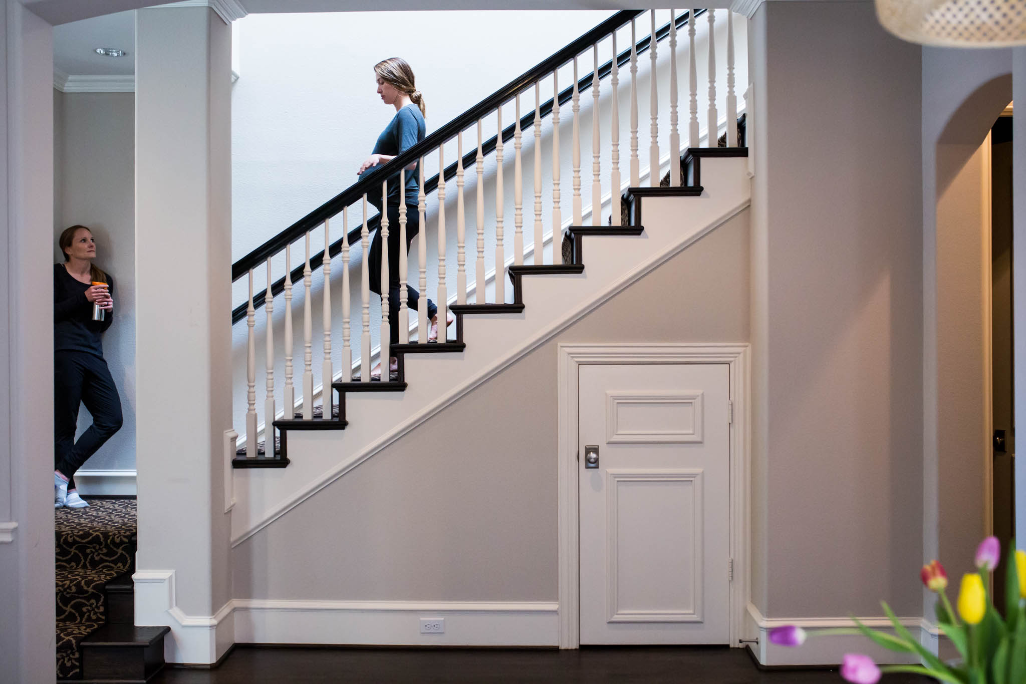 Lawren Rose Photography, a dallas birth photographer, takes a photo of a laboring mom walking up and down the stairs during a home birth