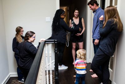 Lawren Rose Photography, a dallas birth photographer, takes a picture of a mom surrounded by her supportive birth team during active labor