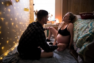 Birth Photographer in Denton, Lawren Rose Photography takes a picture during a home birth while husband supports mom as she enters active labor